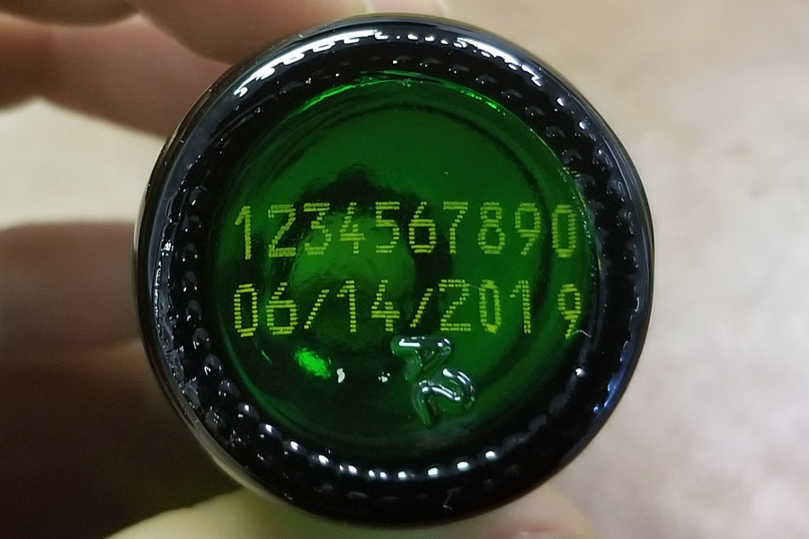 glass green bottle with yellow lot and expiration number on bottom side