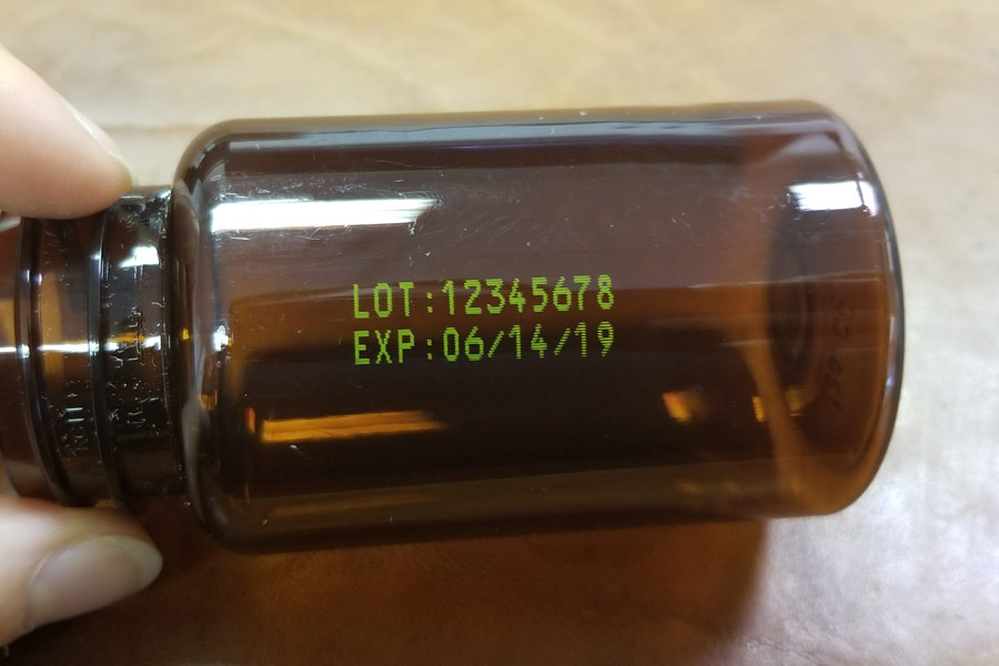 Plastic amber bottle. lot and expiration date. yellow ink