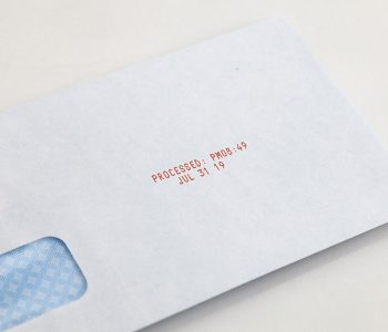 envelope with processed date and time in red ink